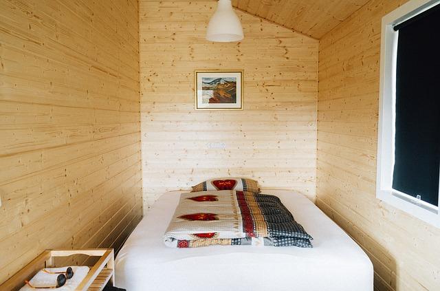 postel v dřevěné místnosti
