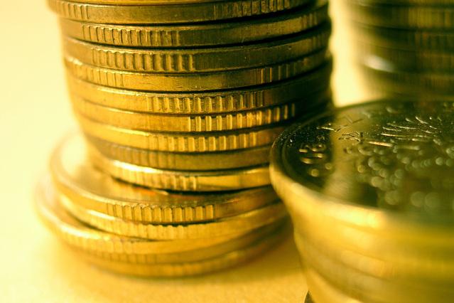 zlaté mince naskládané do sloupců na sobě